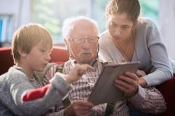 opa met kleinkinderen op de bank met een tablet