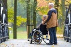 man duwt vrouw in rolstoel in park